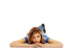 Mujer adolescente pensativa que miente en el piso Foto de archivo libre de regalías