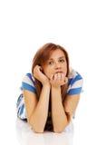 Mujer adolescente pensativa que miente en el piso Imagen de archivo libre de regalías