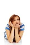 Mujer adolescente pensativa que miente en el piso Foto de archivo