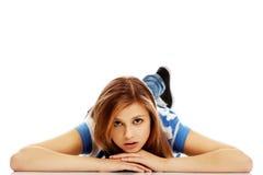Mujer adolescente pensativa que miente en el piso Fotografía de archivo