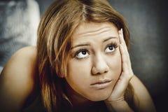 Mujer adolescente pensativa que mira para arriba Foto de archivo libre de regalías