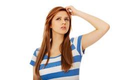Mujer adolescente pensativa que rasguña su cabeza Imagen de archivo
