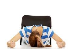 Mujer adolescente preocupante que duerme en el escritorio Imágenes de archivo libres de regalías