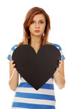 Mujer adolescente preocupante que lleva a cabo el corazón de papel negro Fotos de archivo
