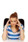 Mujer adolescente preocupante que se sienta detrás del escritorio Fotos de archivo