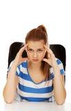 Mujer adolescente preocupante que se sienta detrás del escritorio Imagen de archivo