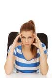 Mujer adolescente preocupante que se sienta detrás del escritorio Imágenes de archivo libres de regalías