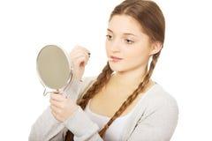 Mujer adolescente que aplica el lápiz labial que mira el espejo Imágenes de archivo libres de regalías