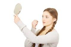 Mujer adolescente que aplica el lápiz labial que mira el espejo Foto de archivo