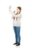 Mujer adolescente que aplica el lápiz labial que mira el espejo Fotos de archivo