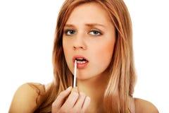 Mujer adolescente que aplica lustre del labio Foto de archivo