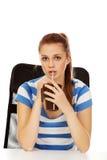 Mujer adolescente que bebe algo a través de la paja Fotografía de archivo