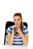 Mujer adolescente que bebe algo a través de la paja Fotografía de archivo libre de regalías