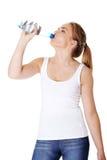 Mujer adolescente que bebe el agua mineral Foto de archivo