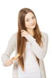 Mujer adolescente que cepilla su pelo Imagen de archivo