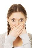 Mujer adolescente que cubre su boca Fotos de archivo
