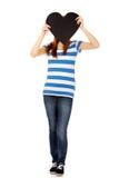 Mujer adolescente que cubre su cara con el corazón de papel Fotos de archivo