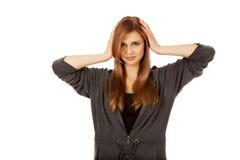 Mujer adolescente que cubre sus oídos Imagen de archivo