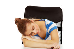 Mujer adolescente que duerme en el escritorio Imágenes de archivo libres de regalías