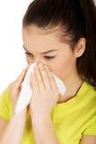 Mujer adolescente que estornuda al tejido Imagen de archivo libre de regalías
