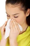 Mujer adolescente que estornuda al tejido Imagenes de archivo