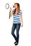 Mujer adolescente que grita a través del megáfono Fotos de archivo