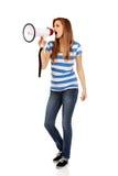 Mujer adolescente que grita a través del megáfono Imágenes de archivo libres de regalías