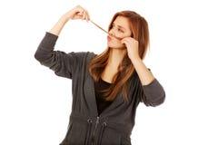 Mujer adolescente que hace el bigote del pelo Imágenes de archivo libres de regalías