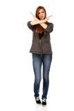 Mujer adolescente que hace la muestra de la parada con las manos cruzadas Imagenes de archivo