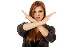 Mujer adolescente que hace la muestra de la parada con las manos cruzadas Foto de archivo libre de regalías