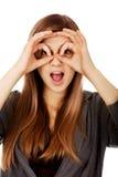 Mujer adolescente que hace las manos de los prismáticos Imagen de archivo