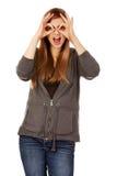 Mujer adolescente que hace las manos de los prismáticos Foto de archivo libre de regalías