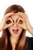 Mujer adolescente que hace las manos de los prismáticos Fotos de archivo