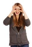 Mujer adolescente que hace las manos de los prismáticos Fotografía de archivo libre de regalías