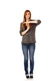 Mujer adolescente que hace un símbolo de rotura Foto de archivo libre de regalías