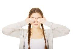 Mujer adolescente que la cubre ojos Fotografía de archivo