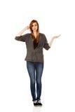 Mujer adolescente que lleva a cabo algo en la palma abierta y que piensa en algo Imagen de archivo