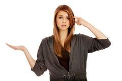 Mujer adolescente que lleva a cabo algo en la palma abierta y que piensa en algo Imagenes de archivo