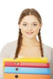 Mujer adolescente que lleva a cabo carpetas Imágenes de archivo libres de regalías