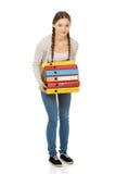 Mujer adolescente que lleva a cabo carpetas pesadas Imagenes de archivo