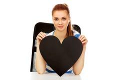 Mujer adolescente que lleva a cabo el corazón de papel negro Imagenes de archivo
