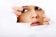 Mujer adolescente que mira furtivamente a través del agujero en el papel Imagen de archivo libre de regalías