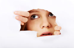 Mujer adolescente que mira furtivamente a través del agujero en el papel Foto de archivo libre de regalías