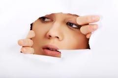 Mujer adolescente que mira furtivamente a través del agujero en el papel Fotos de archivo