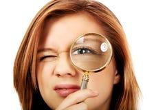 Mujer adolescente que mira a través de una lupa Imagen de archivo libre de regalías