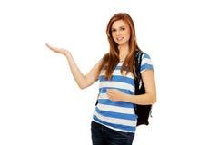 Mujer adolescente que muestra algo en la palma abierta Imagen de archivo
