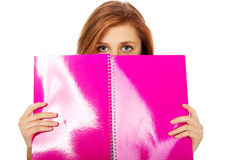 Mujer adolescente que oculta su cara detrás de un cuaderno Fotografía de archivo