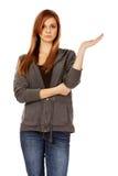 Mujer adolescente que presenta algo en la palma abierta Fotos de archivo