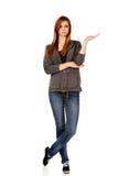 Mujer adolescente que presenta algo en la palma abierta Fotos de archivo libres de regalías
