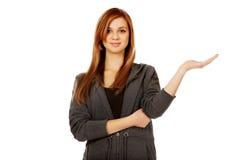 Mujer adolescente que presenta algo en la palma abierta Foto de archivo